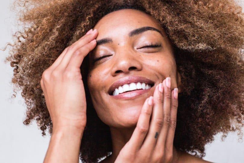 Mulher negra sorrindo com as mãos no rosto.
