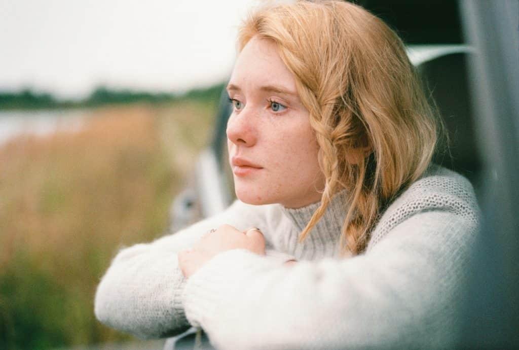Menina olhando pela janela do carro com um semblante pensativo.