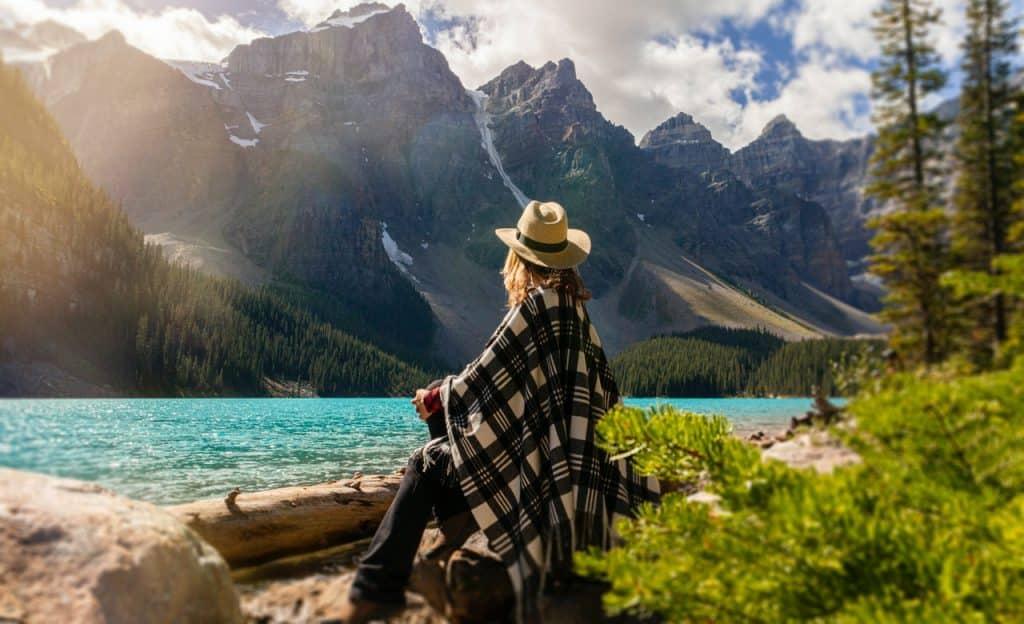 Mulher sentada em uma pedra à beira de um lago. Ela olha para montanhas.