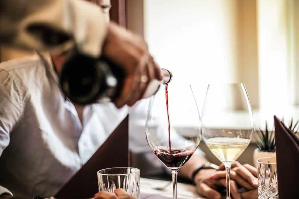 Garçom servindo vinho para um homem