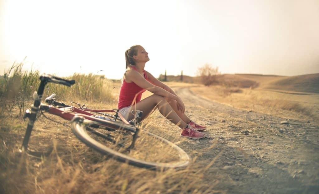 Mulher sentada em uma estrala rural. Ao lado dela, há uma bicicleta deitada.