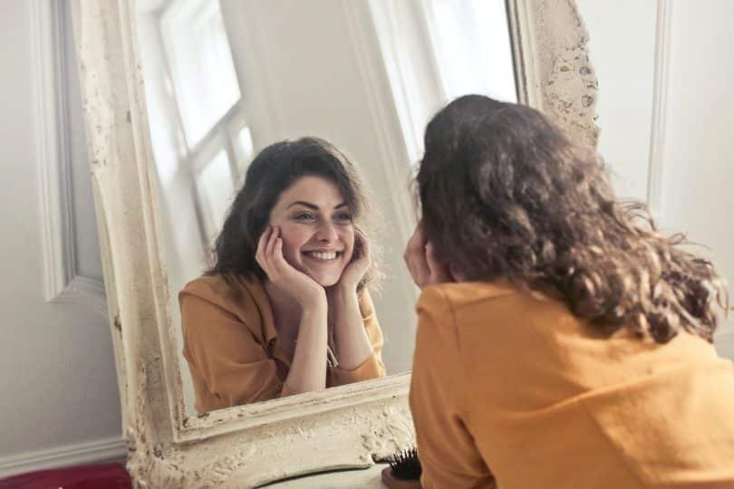 Mulher branca se olhando no espelho sorrindo.