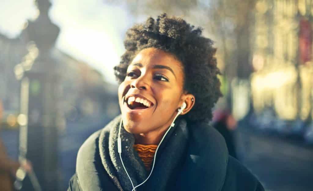 Mulher com fones de ouvido brancos sorri. Ela está em ambiente externo.