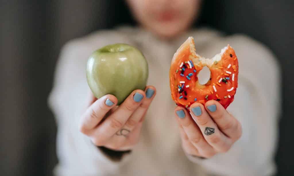 Mulher segura maçã verde e donut.