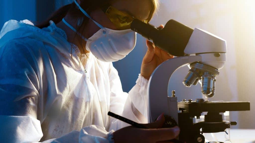 Mulher cientista olhando um microscópio