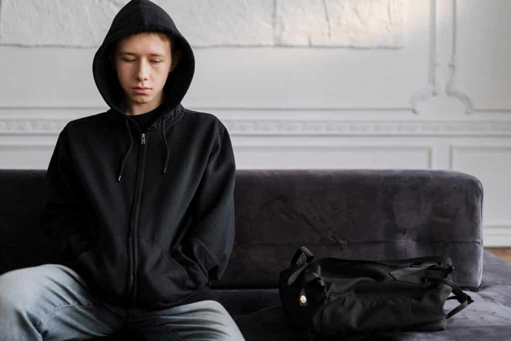 Garoto triste sentado no sofá de sua casa