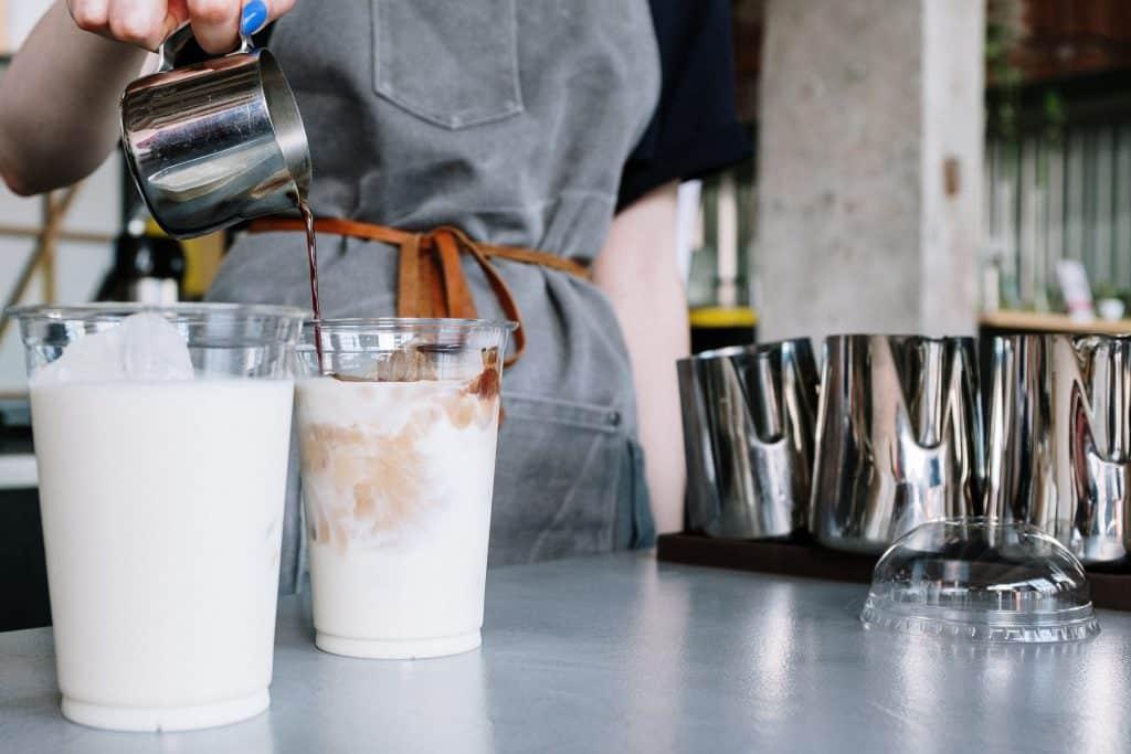 Mulher enchendo um copo com leite