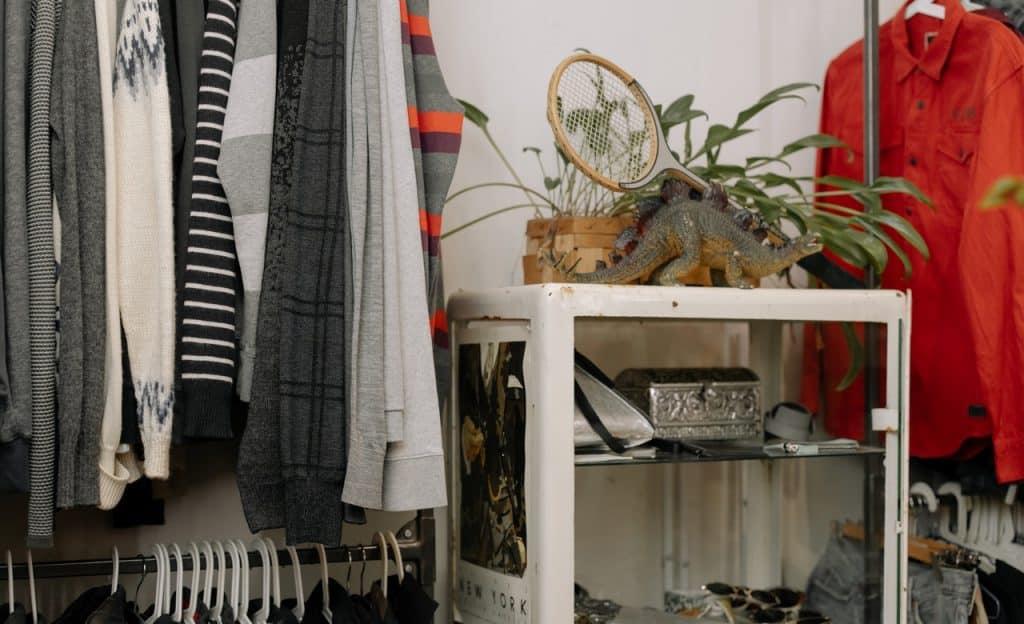 Roupas e pertences pessoais organizados em cabides e estante.