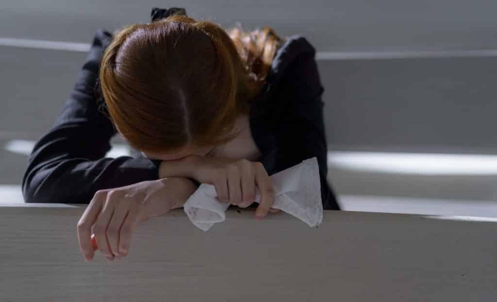 Mulher apoiada em estrutura de madeira branca. Sua cabeça está deitada sobre os braços e uma das mãos segura um lenço.