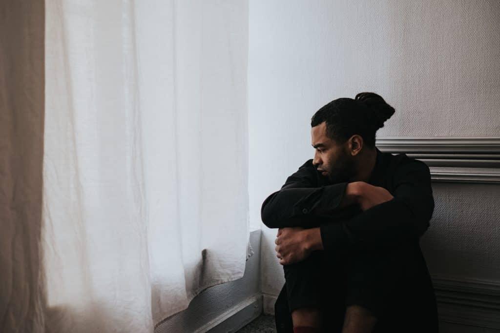 Homem sozinho triste enquanto olha para a janela
