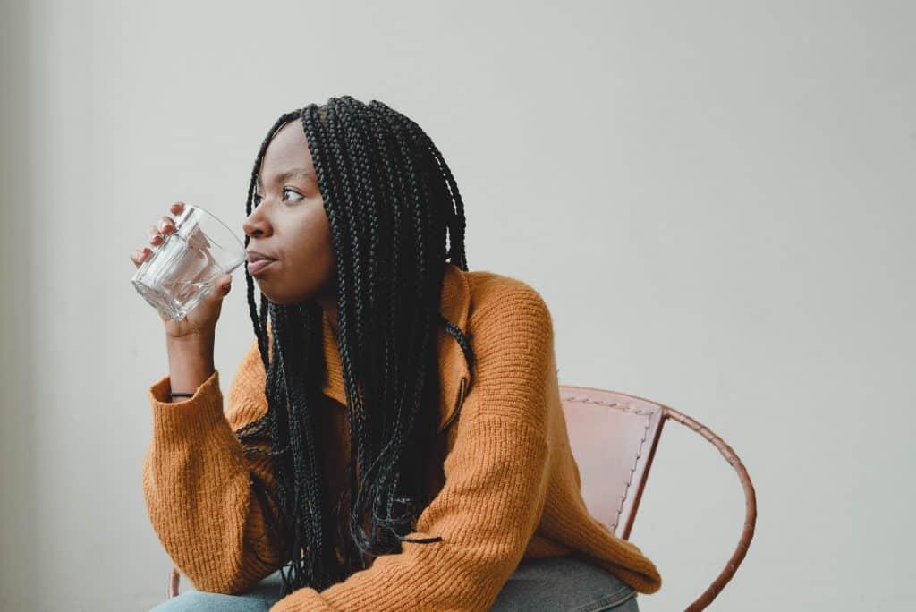 Mulher refletindo enquanto bebe um copo de água