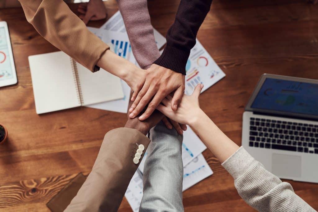 Pessoas de uma equipe de trabalho estendendo e sobrepondo suas mãos demonstrando colaboração