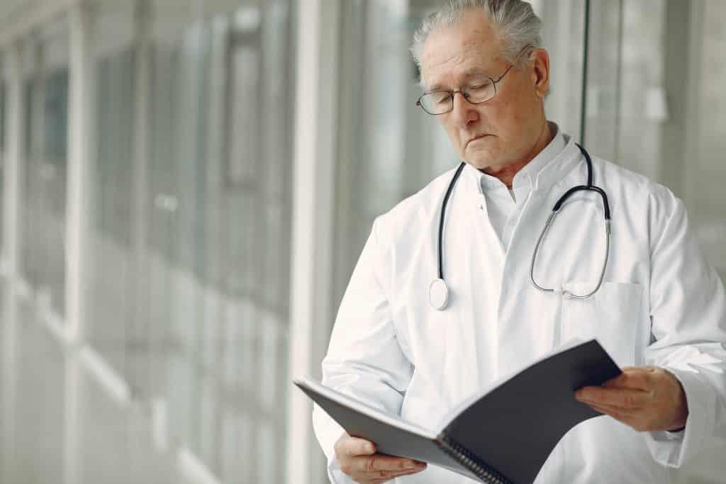 Doutor em pé segurando e olhando para uma pasta