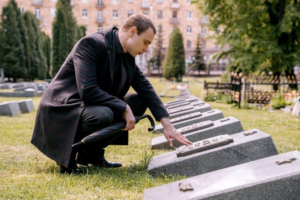 Homem em frente ao túmulo de alguém com semblante triste.