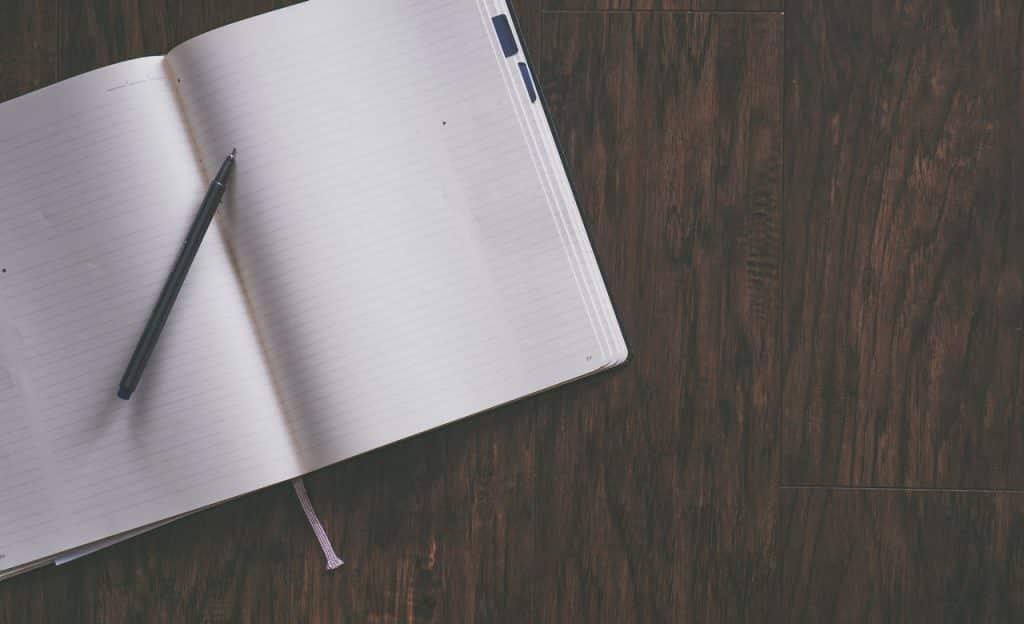 Caderno sobre superfície de madeira. Sobre ele, há uma caneta.