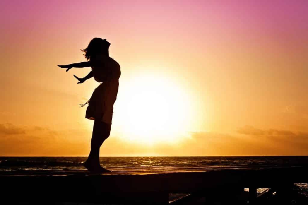 Silhueta de uma mulher na praia com o sol se pondo ao fundo.