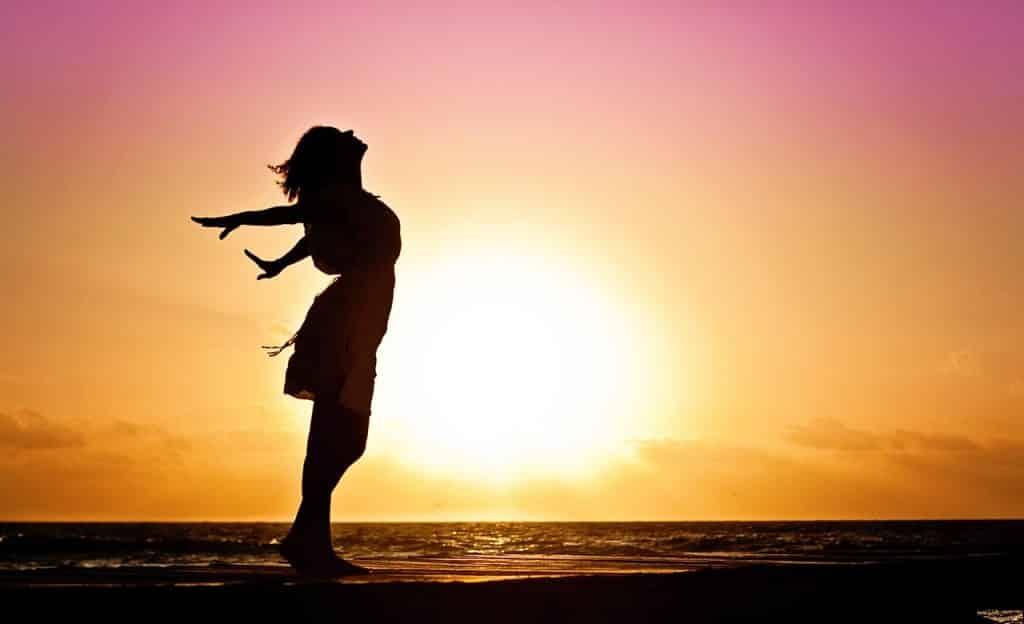 Mulher inclinada para trás com os braços abertos. Ela está em praia. Ao fundo, há o sol.