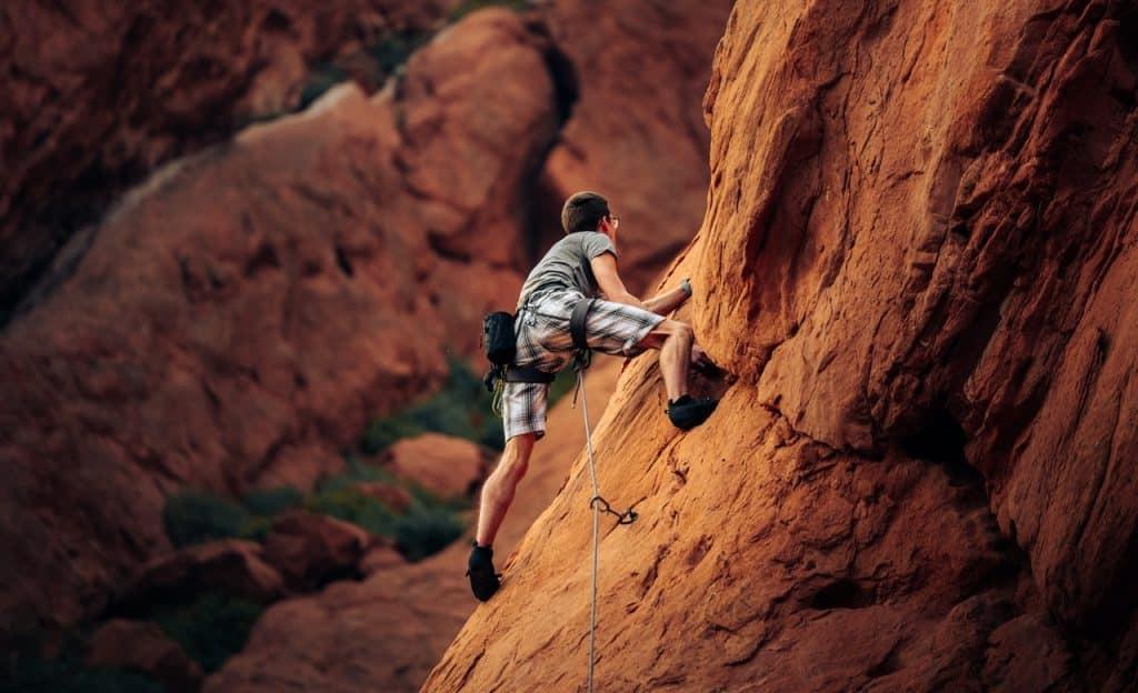 Homem escala montanha.
