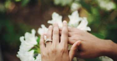 Uma mão com uma aliança no dedo anelar esquerdo