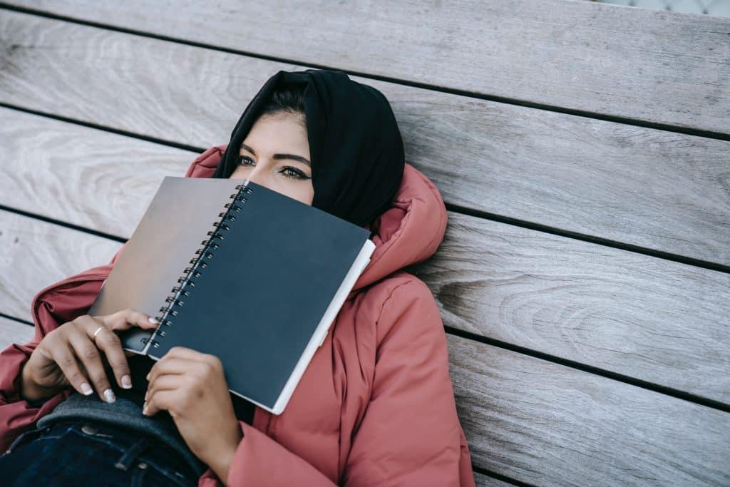 Mulher deitada no chão segurando um caderno em cima do seu rosto