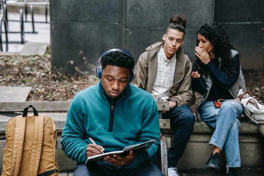 Pessoas conversando ao fundo de um homem negro escrevendo num caderno.