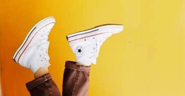 Plano de fundo amarelo com pés calçando sapatos brancos à frente