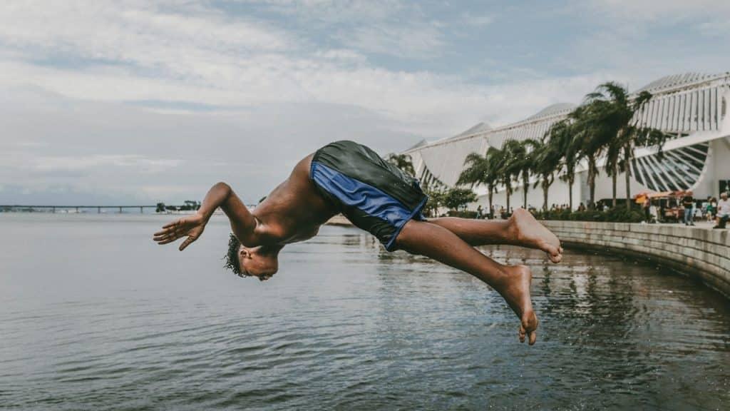 Menino está mergulhando no mar em frente ao Museu do Amanhã no Rio de Janeiro.