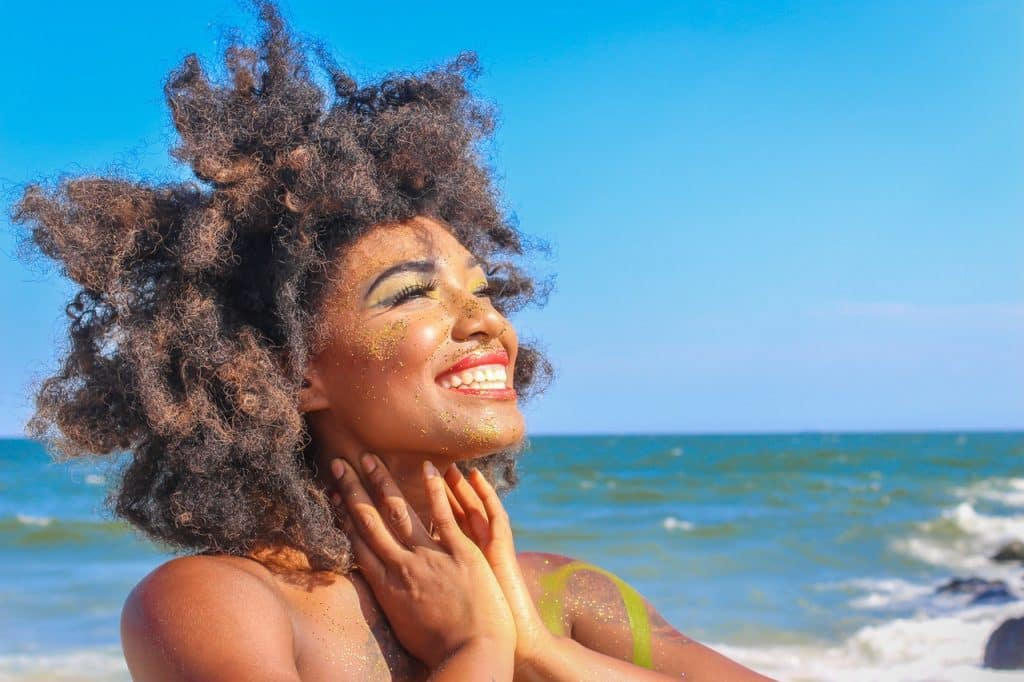 Mulher negra sorrindo na praia.