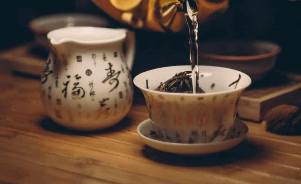 Chá sendo servido em xícara de porcelana branca.