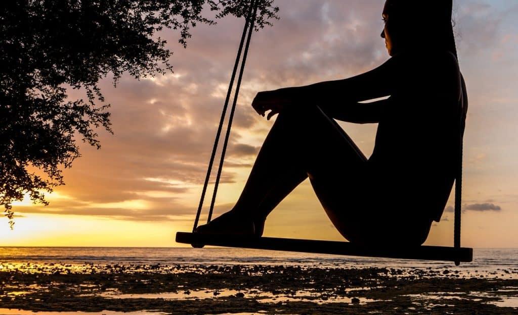 Mulher em balanço observa o horizonte.