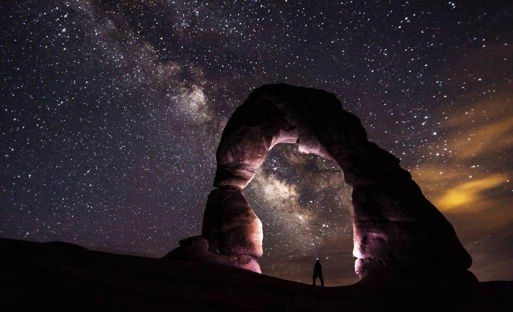 Pessoa sob arco de pedra à noite. O céu é estrelado.