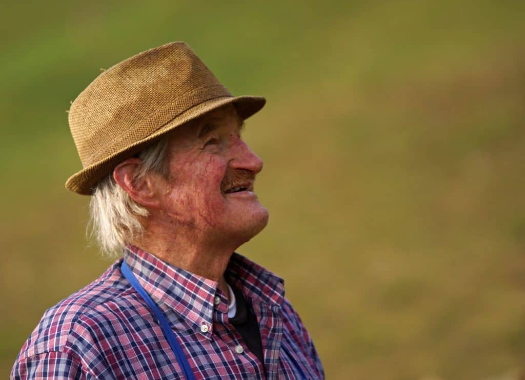 Idoso branco usando chapéu e sorrindo.
