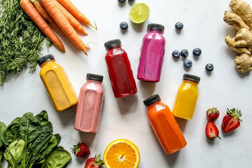 Frutas, verduras, legumes e sucos dispostos em cima de uma mesa