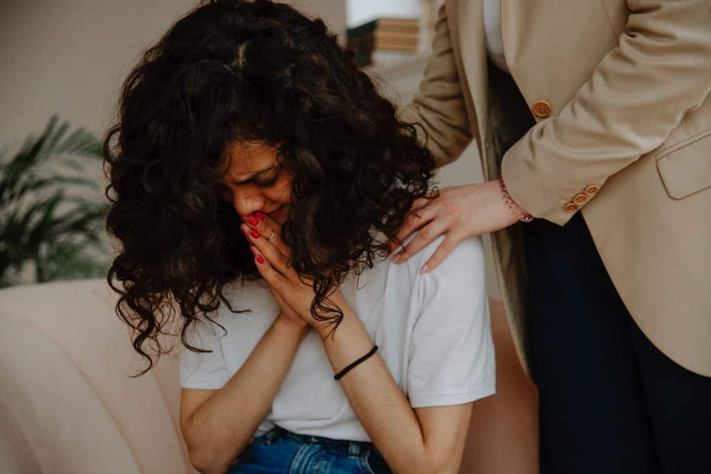 Mulher chorando com as mãos unidas