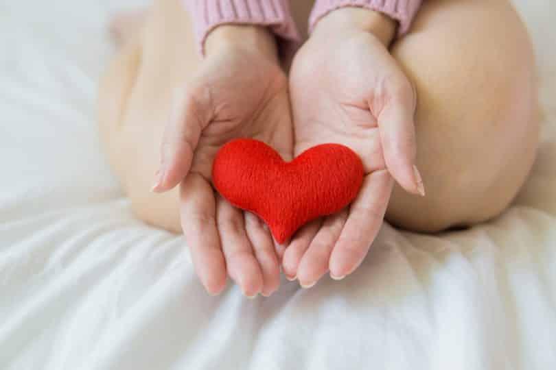 Mulher com um coraçãode pelúcia em suas mãos