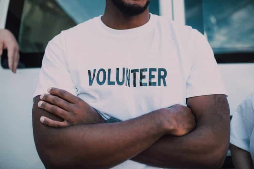 "Homem negro usando camiseta escrito ""volunteer""."