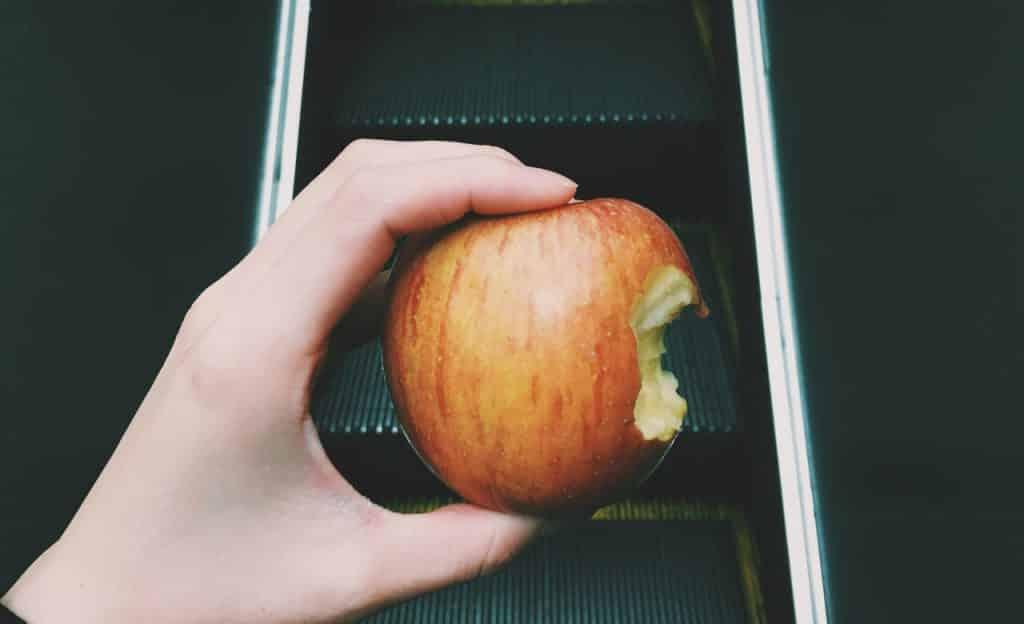 Mulher segura maçã mordida. Ao fundo, há uma escada rolante.