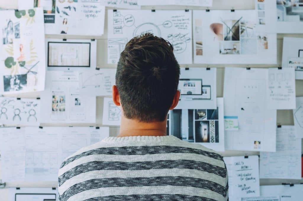 Homem olhando para um mural de ideias.