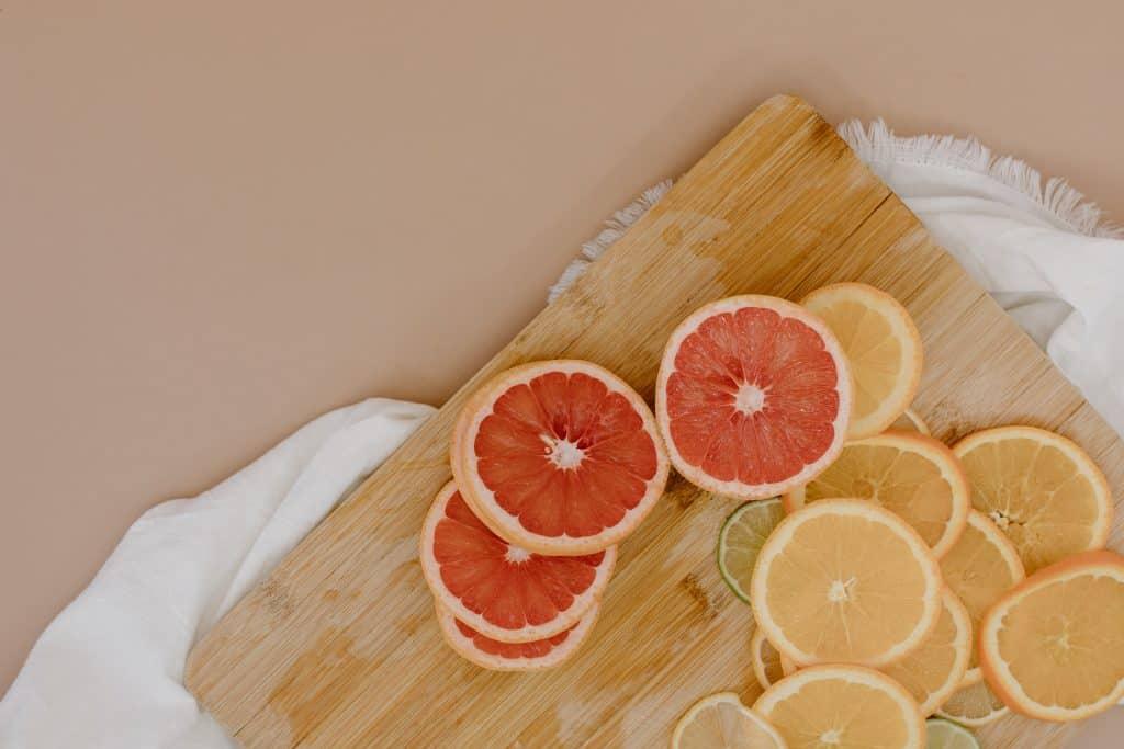 Rodelas de laranjas e limões em cima de uma tábua de madeira