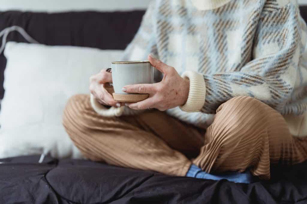 Mulher segurando xícara de café com as mãos.