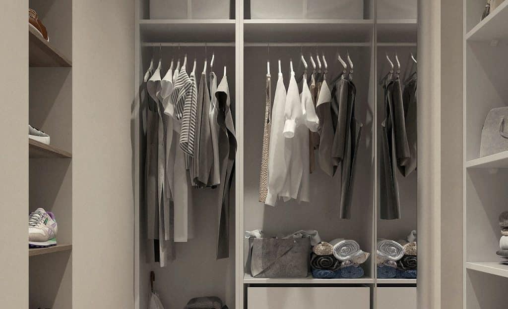 Armário organizado com roupas e calçados variados.