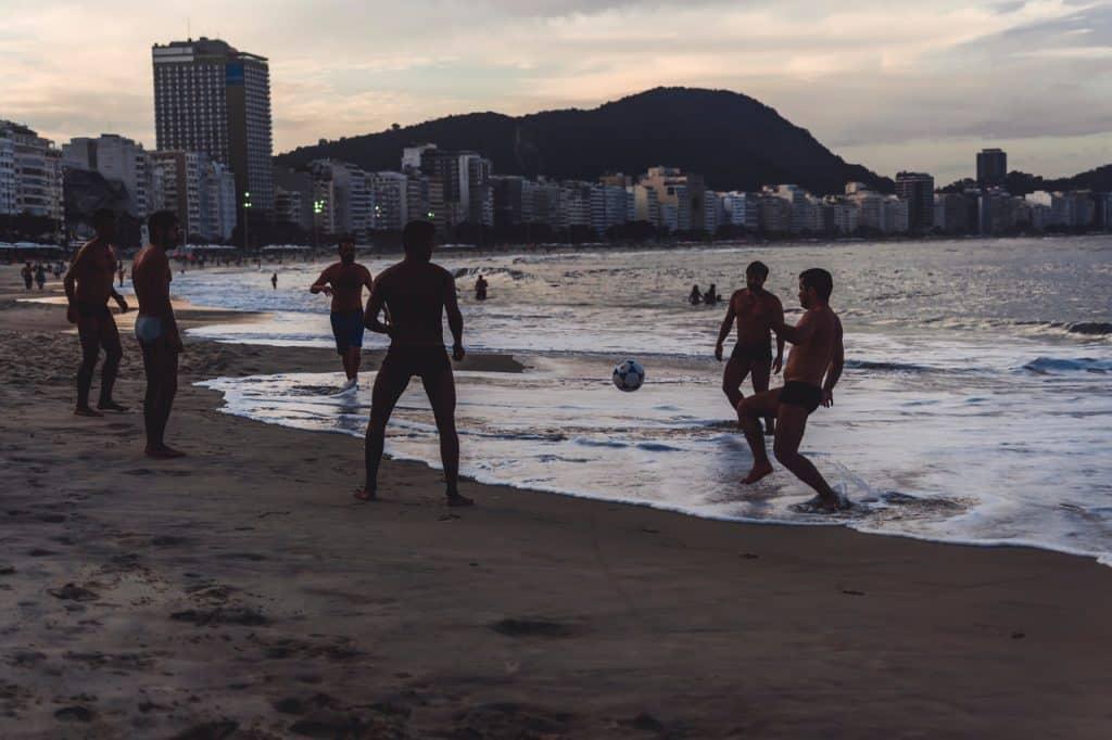 Homens jogando bola em uma praia do Rio de Janeiro.