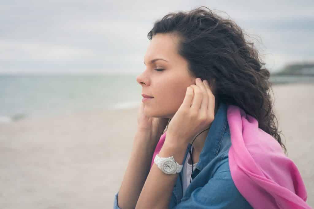 Mulher branca na praia com os olhos fechados e fones de ouvido.
