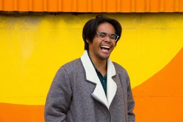 Homem marrom de óculos sorrindo.