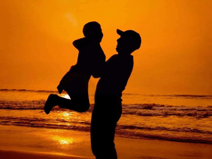 Silhueta de homem segurando criança numa praia.