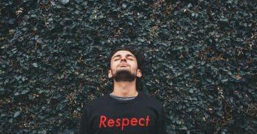 Homem branco com a cabeça levantada e parede de folhas ao fundo.