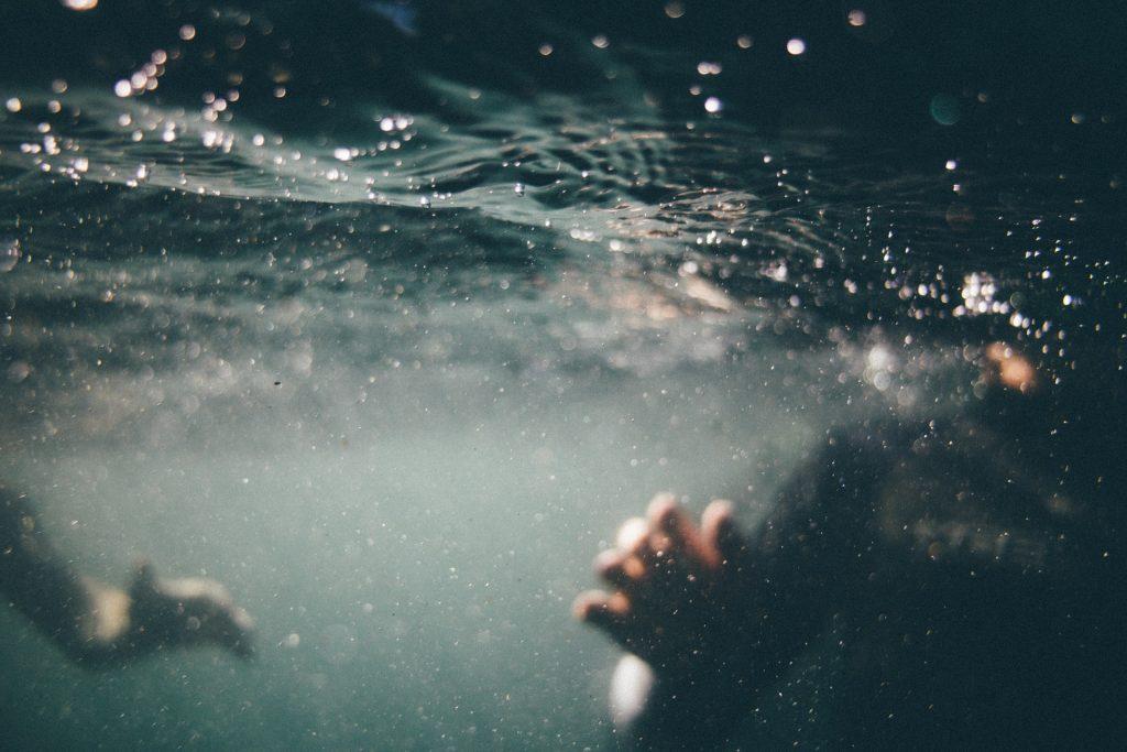 Mãos se mexendo embaixo da água.
