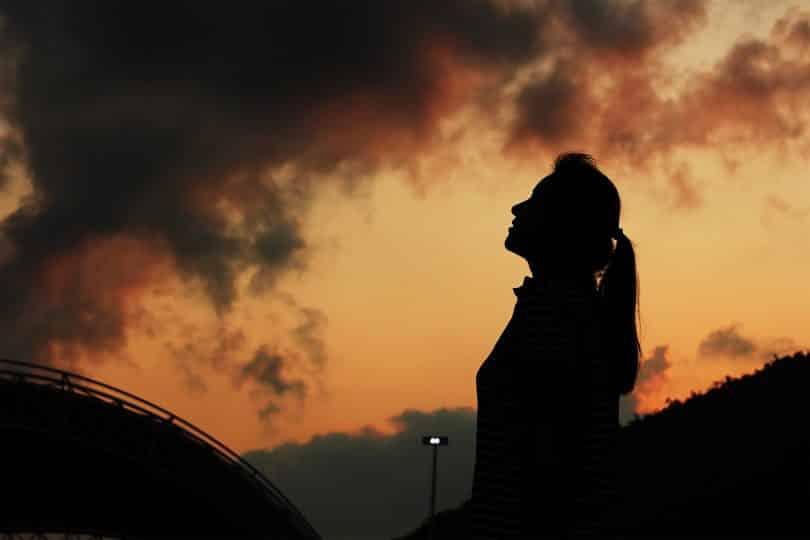 Silhueta de mulher durante o pôr do sol.