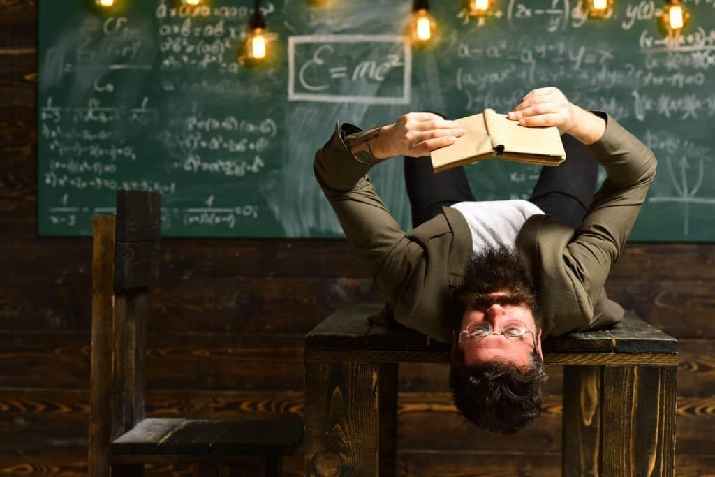 Homem deitado em uma mesa de sala de aula lendo um livro