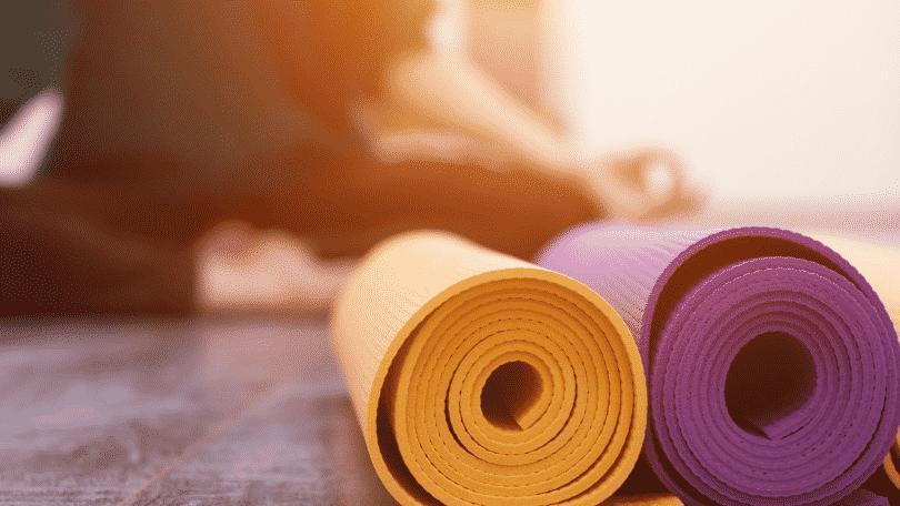 Pessoa meditando com tapetes de yoga dobrados na frente